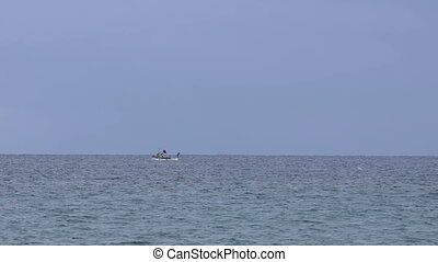 Small fisher boat in far away in a mediterranean sea