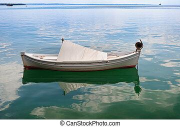 Small fishing boat at sea surface