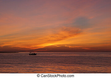 Small fishing boat in the sea at sunset