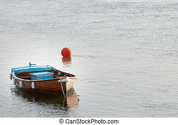 Small fishing boat moored in the water ready for sailing