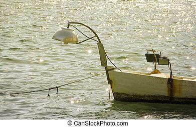 Small fishing boat on sunset