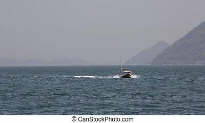 Small fishing boat with waves crashing
