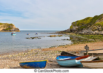 Small fishing boats in Lulworth Cove. Dorset, England.