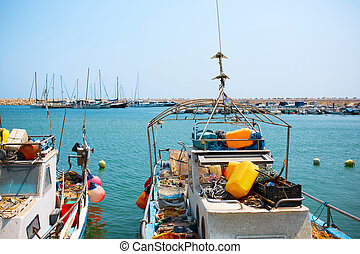 Small fishing boats in port with fishing net and equipment