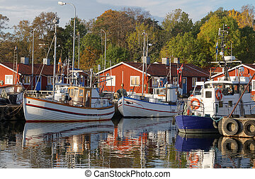 Small fishing boats in the harbor reflecting in the water