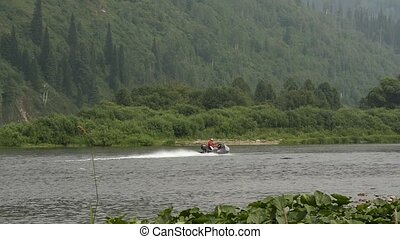 Small fishing powerboat moving quickly on the river in a summer time. slow motion