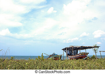 Small fishing wooden boat on the shore