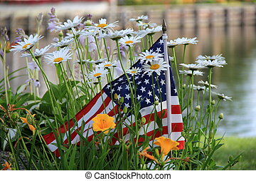 Small flag in garden of daisies