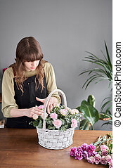 Small flower shop. Woman florist creating beautiful bouquet in a wicker basket. Work in flower shop. Flowers delivery