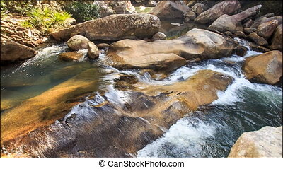 Small Foamy River Flow among Brown Rocks in Park