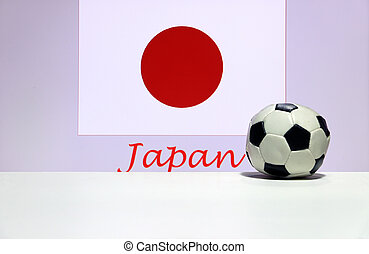 Small football on the white floor and Japanese nation flag with the text of Japan background. The concept of sport, Japan is one of the finalists in football tournament of the world.