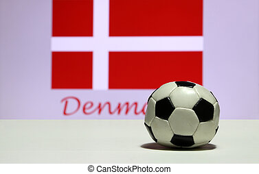 Small football on the white floor and out focus white cross on red of Danish nation flag background with Denmark text.