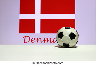 Small football on the white floor and white cross on red of Danish nation flag background with Denmark text.