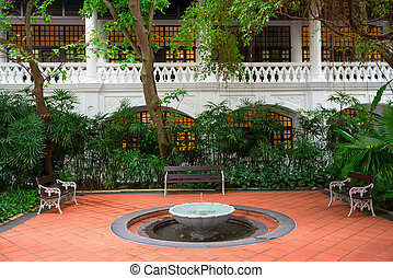 Small fountain in a garden with benches and white classical...