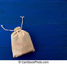 small full canvas bag with ties, blue wooden background