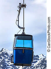 small funicular in front of snowy mountains