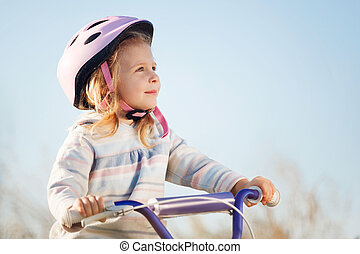 Small funny kid riding bike with training wheels.