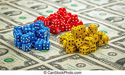 Small game dice of different colors in piles on cash