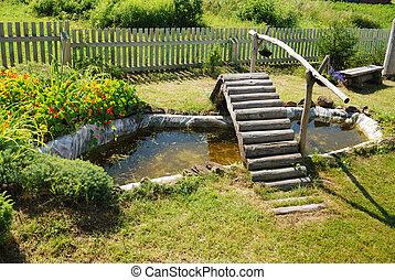 small garden pond with wooden bridge
