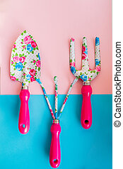 Small garden shovel and rake on a blue and pink background. set of rake steel and shovel isolated. Metal gardening hoe weeding chisel trowel and rake agriculture concept.