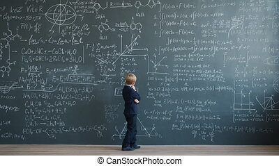 Small genius thinking about science looking at blackboard ...