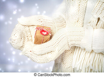 Small gift box in hands with white gloves