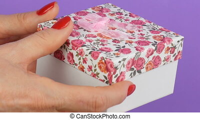 Small gift box with a floral print and a pink bow that is...