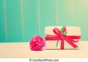 Small gift box with carnations on teal colored wood