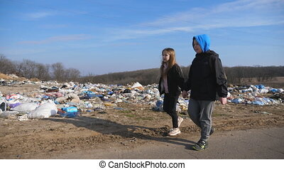 Small girl and boy holds hands of each other and goes along road to school against the background of garbage dump. Little sad children walks near junkyard at countryside. Environmental pollution.