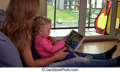 Small girl and her mother watching family photos on tablet computer screen