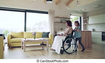 Small girl and her senior grandmother in wheelchair indoors at home.