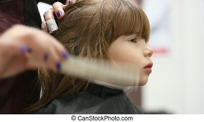 Small girl at hairdressing saloon