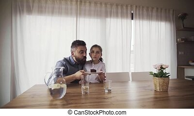 Small girl bringing cake to her father indoors at home, ...