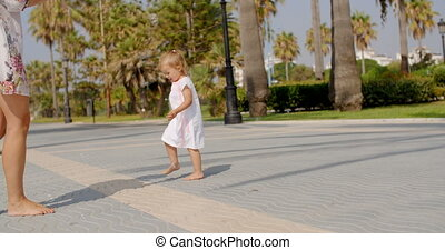 Small Girl Chasing Air Bubbles on Exotic Beach Promenade at...