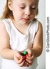 Small girl chews the candies - Bubble Gums in the hands of...