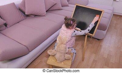 Small girl cleaning blackboard