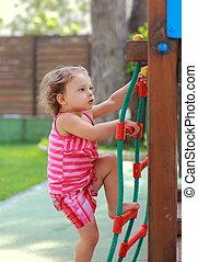 Small girl climbing up on children activity ladder outdoors ...