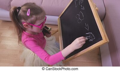 Small girl drawing doll on blackboard