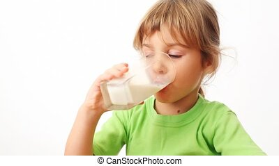 small girl drinks milk from glass and starts up bubbles in it