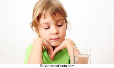small girl drinks water from glass and smiles on white background