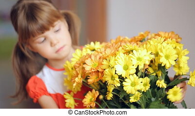 Small girl embraces bunch of yellow flowers