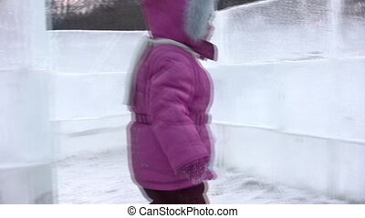 Small girl goes on icy labyrinth, blind alley