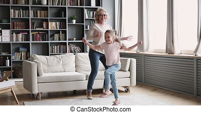 Small girl granddaughter dancing with old grandma in living room