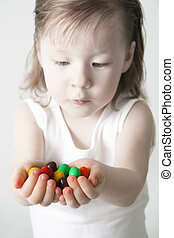 Small girl hold in one's hand the candies - Bubble Gums in...