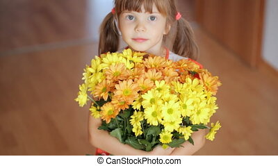 Small girl holds big bunch of yellow flowers