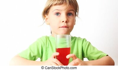 small girl holds in hands glass of juice, drink it and smiles
