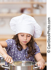 Cute little girl in a chefs toque cooking in the kitchen standing over a large stainless steel pot stirring the contents