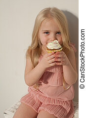 small girl in hand holds a sweet cupcake cake