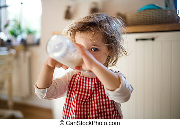 Small girl indoors in kitchen at home, drinking milk from bottle.