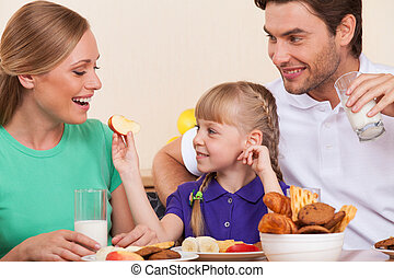 Small girl is feeding her mother with an apple,